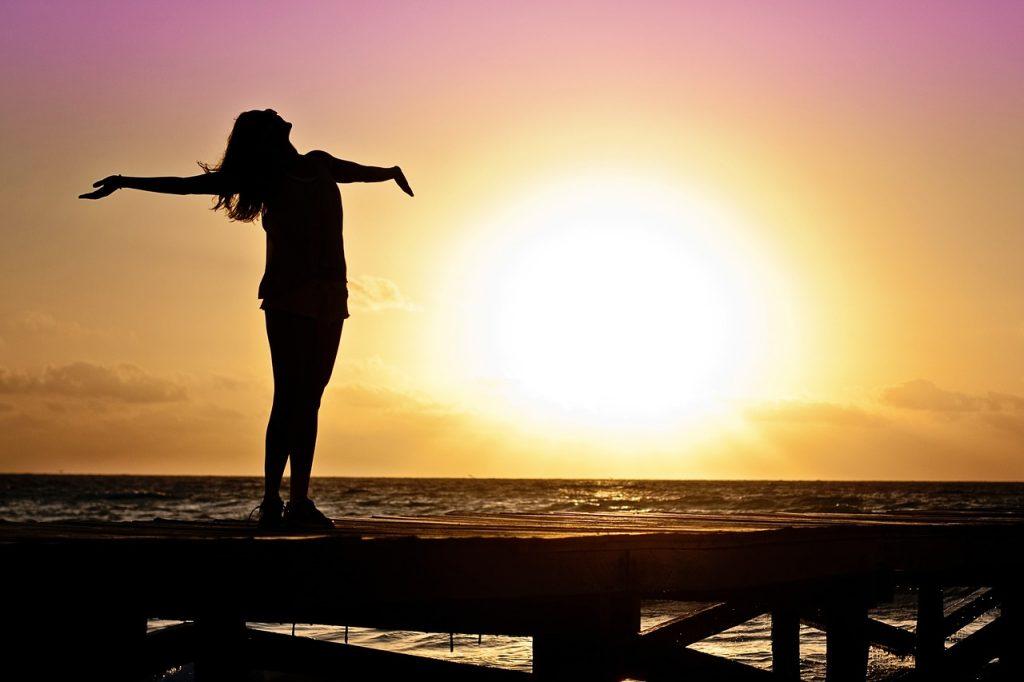 mulher de braços abertos na praia
