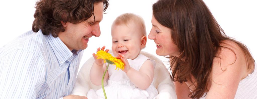 padre, madre e hija sonreindo