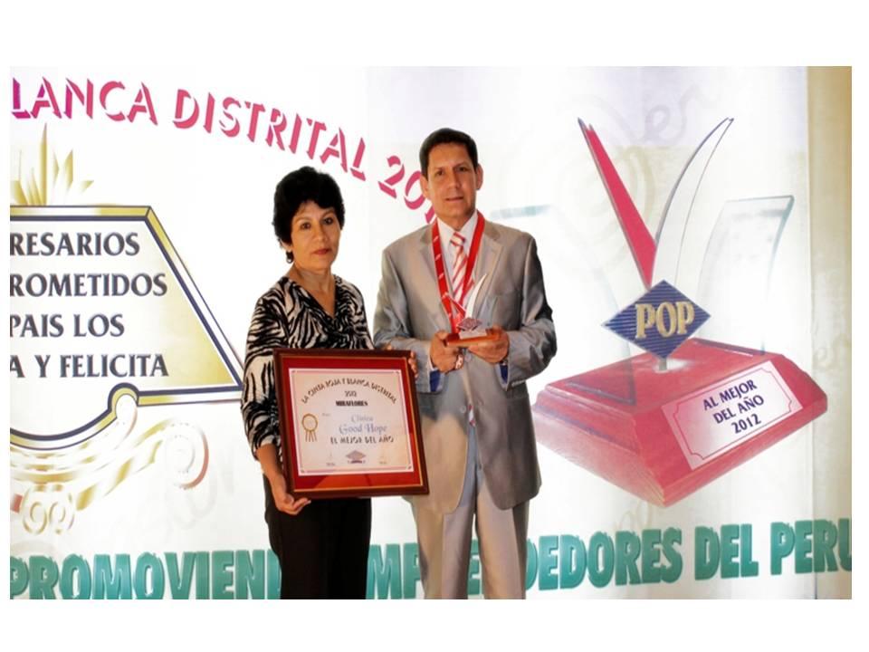 Representante de Peruana de Opinión Pública premia a la clínica, Good hope, en la persona de Luis Barba.