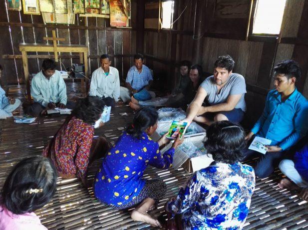 Perrotey haciendo entrega de los libros El Camino a Cristo a pobladores de Laos.