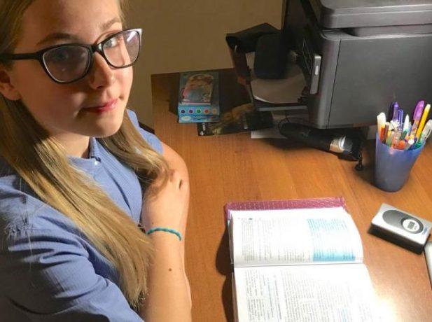 Foto:  La alumna de séptimo grado, Ellina Minina, 13 años, sentada con un libro de texto en su casa en Pavlodar, Kazajistán. (Andrew McChesney / Adventist Mission)