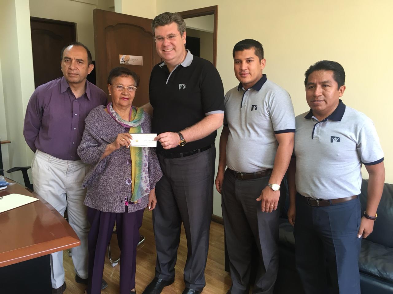 Pr. Kalbermatter junto a la administración de Nuevo Tiempo haciendo la entrega del cheque a Hortencia Fernández