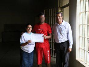 Maria José Aguilar e pastor José Alves entregam certificado para um dos detentos
