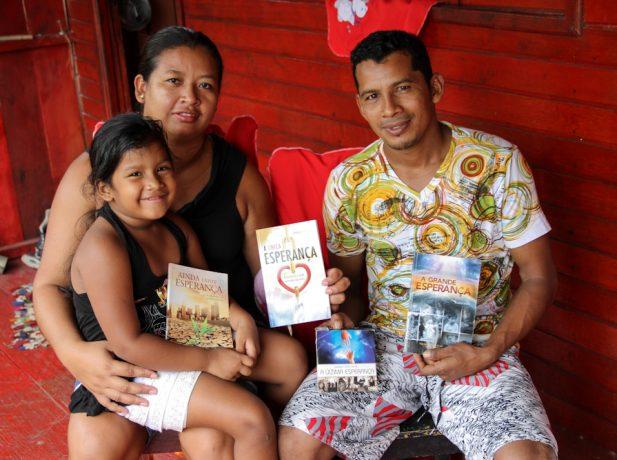 Agnaldo e família exibem livros que contribuíram para que o o jovem deixasse o caminho das drogas e mudasse de vida.