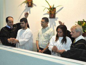 Momento do batismo de Maria Lucia e do marido Geonavi. Um novo recomeço para o casal que espera o nascimento do filho.