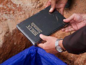 A bíblia sendo colocada entre os alicerces da construção do novo prédio do CASL.