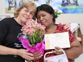Maria Isabel recebe o certificado de batismo e flores da líder de seu Pequeno Grupo, Maria do Carmo