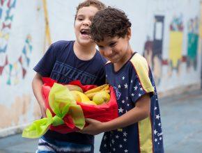 Aventureiros do clube Cosmos Kids ajudam na entrega das cestas para a ONG.