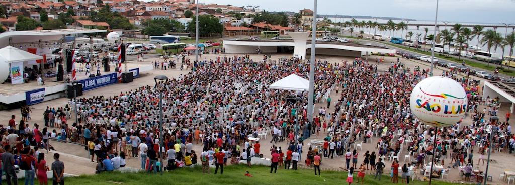 Visão geral dos milhares de jovens participando de culto especial em praça pública.