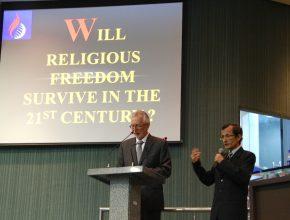 John Graz, sendo traduzido durante palestra, e a pergunta na tela: liberdade religiosa vai sobreviver no século 21?