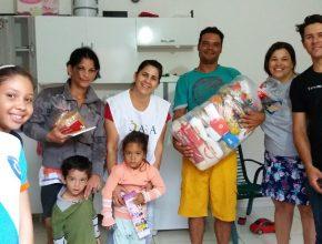 Lucineia Menocci, diretora da ASA, entrega alimentos e brinquedos a família carente de bairro próximo à igreja.