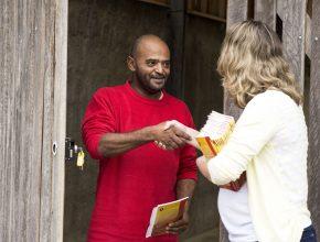Morador recebe livro missionário em Chácara, MG.
