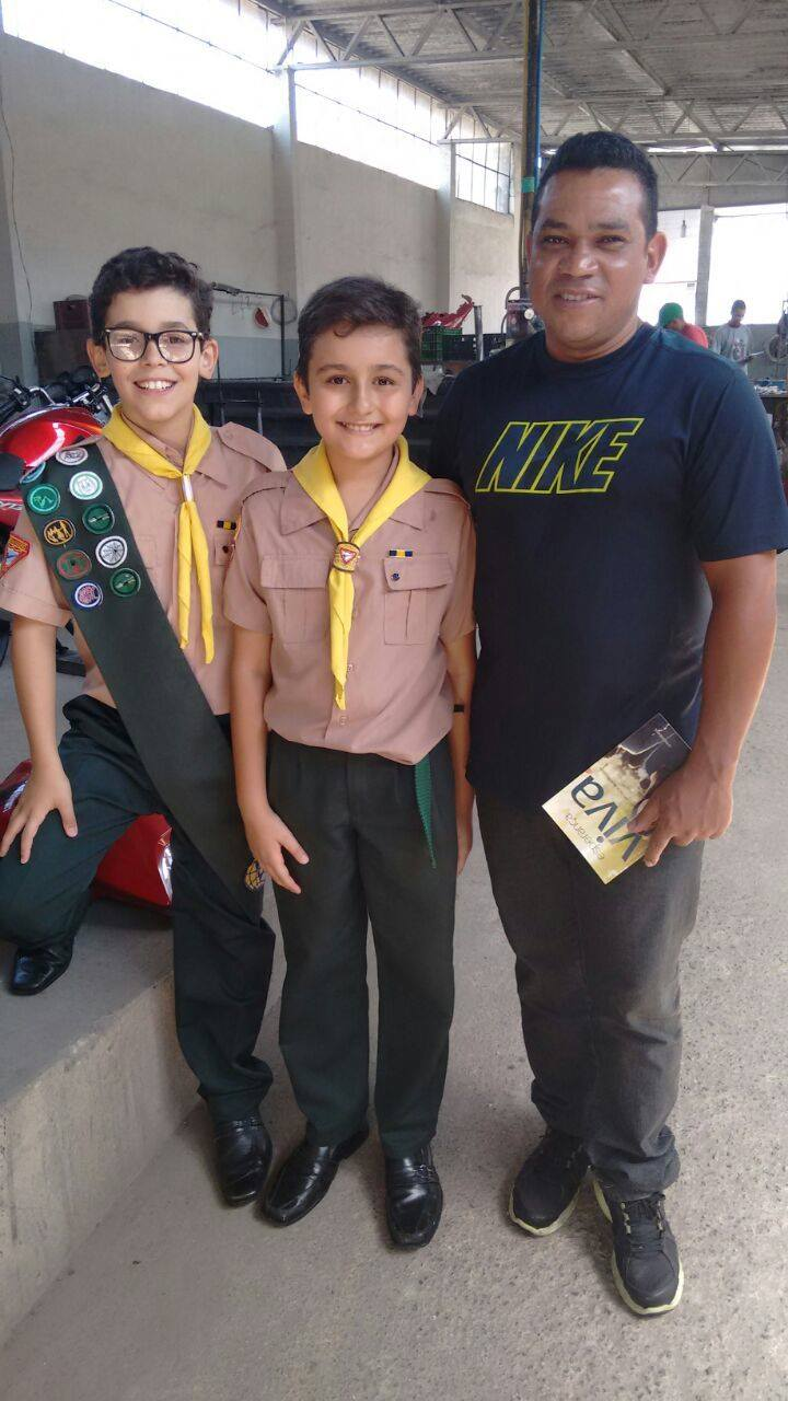 Nicholas, ao centro, e seu amigo, ambos do Clube de Desbravadores Lince, Anápolis, GO, entregando o livro em pontos comerciais.