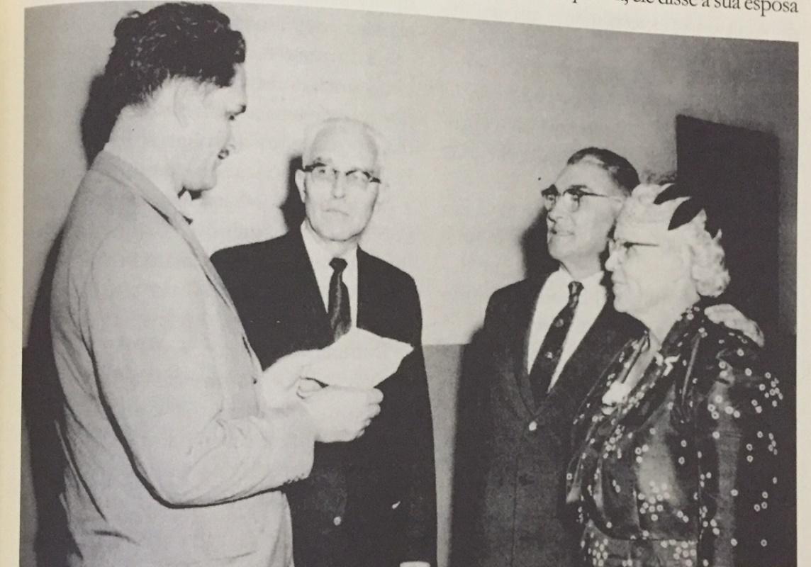 Léo Halliwell (1891-1967) e Jessie (1894-1962) Halliwell, à direita, recebem a notícia do Dr. E.M. Berger, à esquerda, em 1958, de que o governo brasileiro lhes havia outorgado a Ordem Nacional do Cruzeiro do Sul por seu sucesso em limpar a bacia do Amazonas de suas enfermidades e transformá-la em uma região habitável. O Cruzeiro do Sul é a condecoração civil mais importante do Brasil. R.R. Figuhr (1896-1983), centro, presidente da Associação Geral e ex-presidente da Divisão Sul-Americana, observa o acontecimento. (Livro Portadores de Luz, 485).