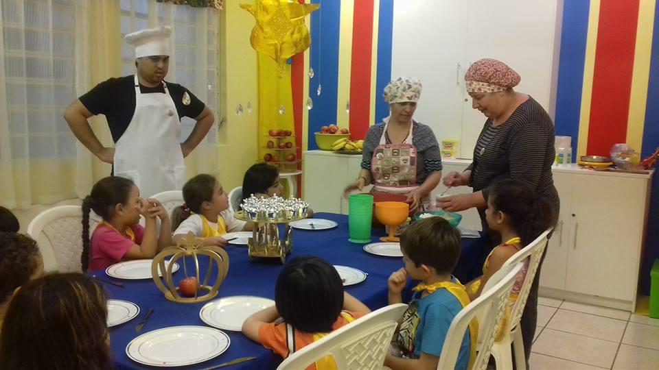 Crianças aprendendo culinária na Escola Cristã de Férias.