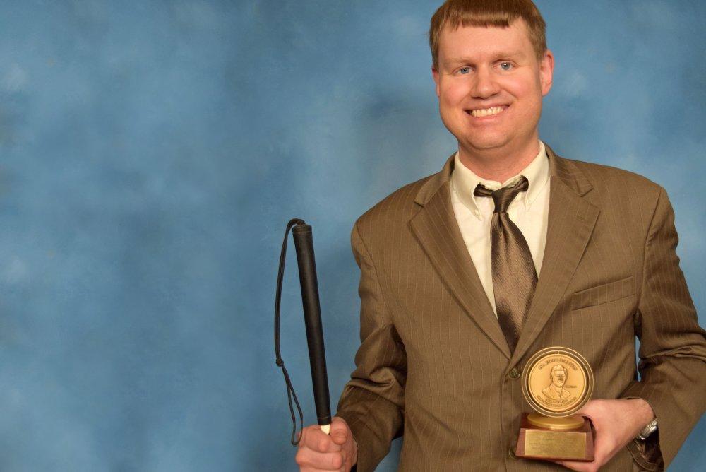 Ray McAllister segurando o Prêmio Dr. Jacob Bolotin por seu trabalho na codificação em braile. (Universidade Andrews)