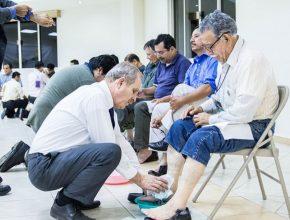 Adan Dyck lava os pés de um homem surdo durante uma das atividades do congresso