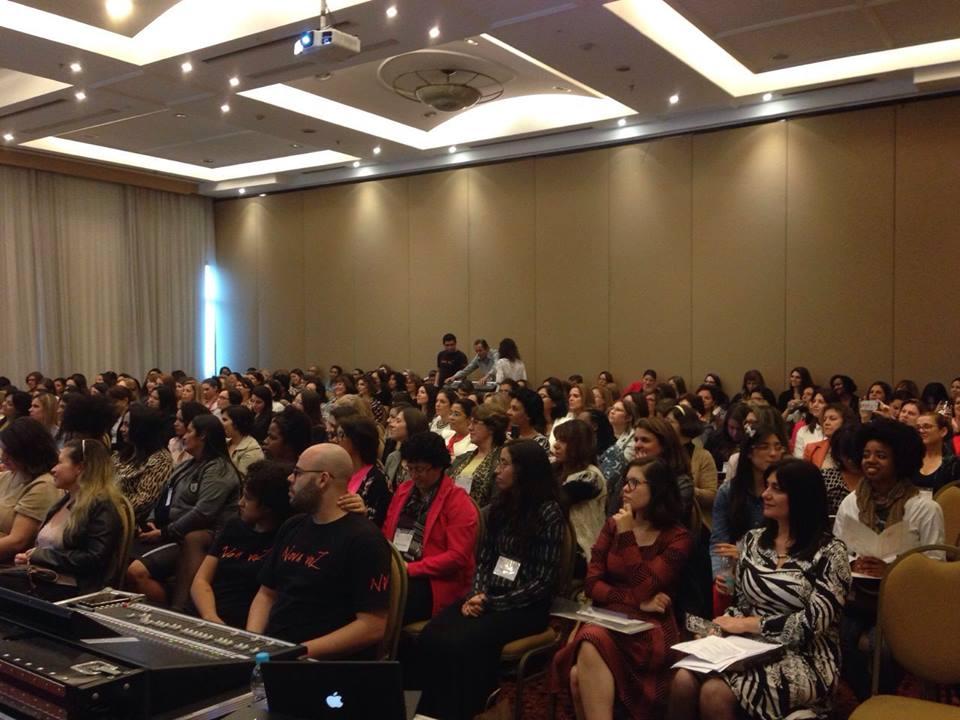 Mulheres reunidas assistindo palestras no Hotel Grand Mercure Ibirapuera.