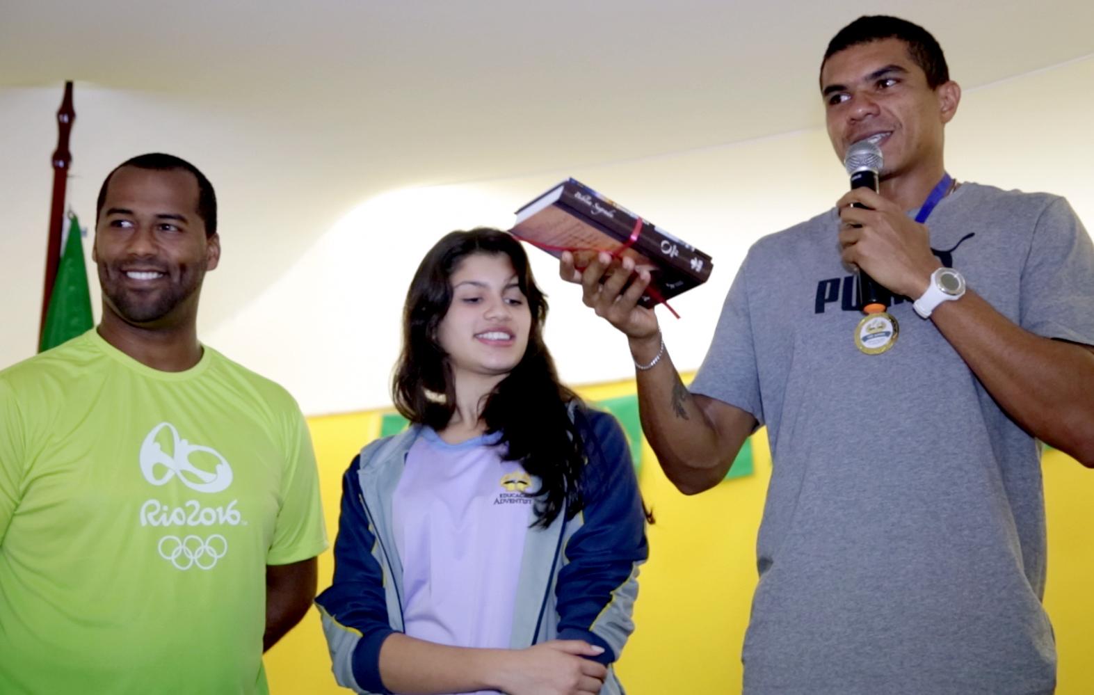 Atleta Olimpico, Éder Souza (dir.), recebe um presente do colégio, das mãos professor  Thiago dos Santos e uma aluna da escola.