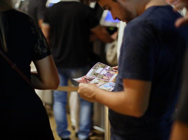 Após ver o filme, jovem lê história em quadrinhos entregue por adventistas. Material ressalta crenças da denominação (foto: Rodrigo Gorski)