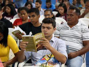 O jovem líder lê atentamente o conteúdo do livro que ganhou.