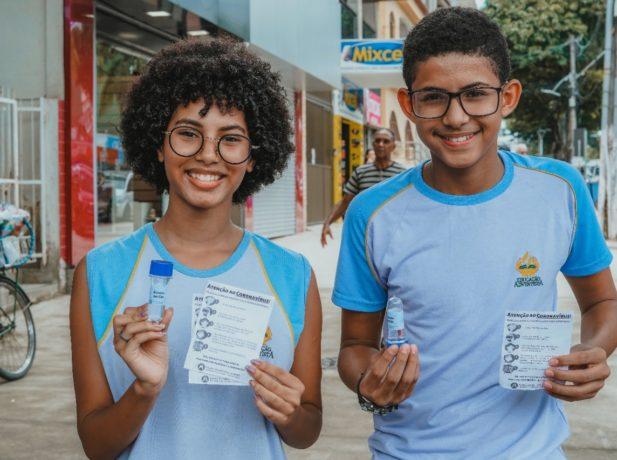 Os alunos Isabela e Nicolas mostram o material entregue à população. (Foto: Arthur Henrique)