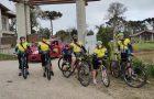 Ciclistas adventistas distribuem livros missionários à comunidade