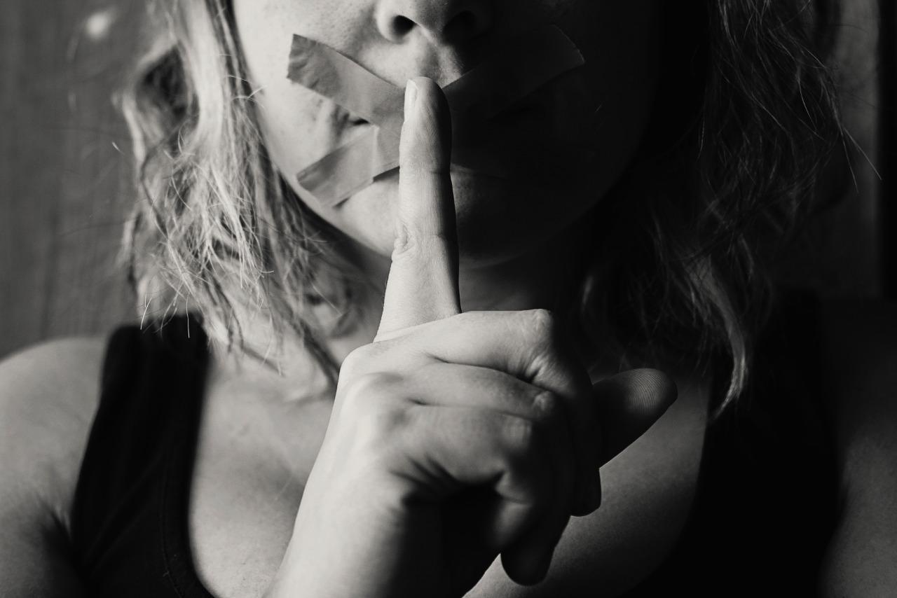 Mulher com fitas na boca e a mão fechada com o dedo sinalizando silêncio. Uma representação do oposto da imagem: quebrar o silêncio.