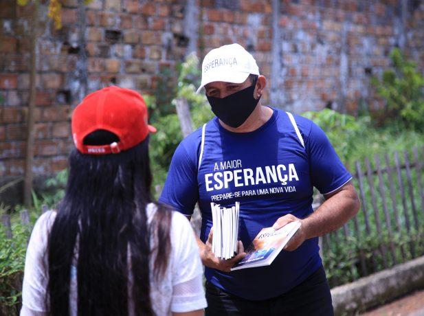 Colaboradores distribuem livros missionários para comunidade local. (Foto: Leonardo Leite)
