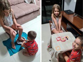 Uma menina loira e um menino loiro, ambos pardos, fazem o lava pés bíblico e tomam suco e comem pão como o símbolo verdadeiro da Páscoa.