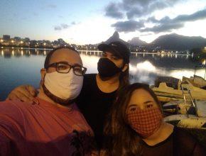 Homem pardo de óculos, mulher parda cabelos castanhos compridos e boné preto e moça parda de cabelos castanhos compridos posam com a Lagoa Rodrigo de Freitas ao fundo.