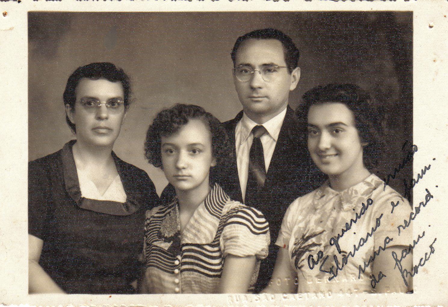 Foto de uma família: homem pardo, de óculos, cabelo curtovestindo terno e gravata. Mulher parda, cabelo curto e castanho com vestido escuro. Duas mocinhas de pele parda, cabelos cacheados, uma séria e outra sorrindo. Filhas do casal de adultos. Foto em preto e branco.