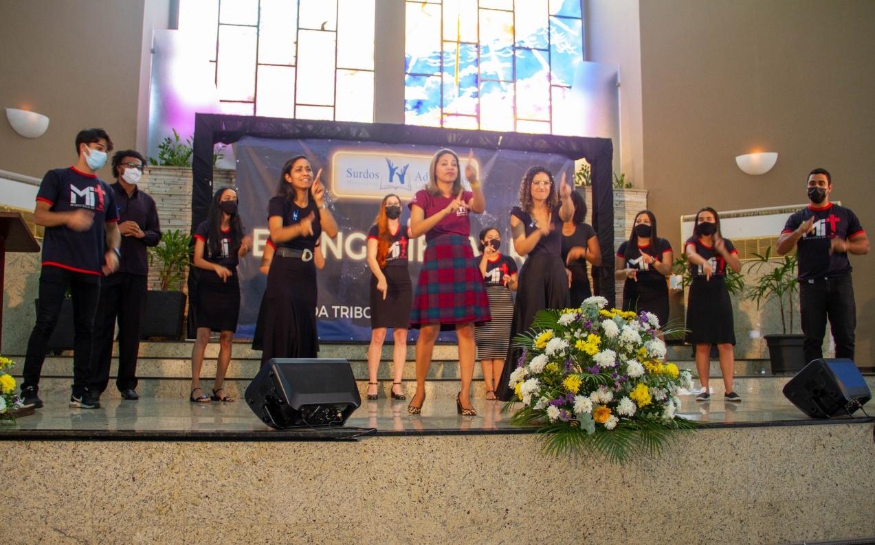 Várias pessoas fazendo gestos na língua de sinais durante um evento evangélico na Igreja Adventista Central Rio.