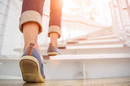 Jovem mulher adulta subindo as escadas com fundo esporte sol