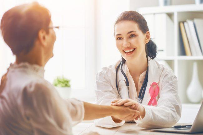 Médica segurando a mão de uma mulher de meia idade