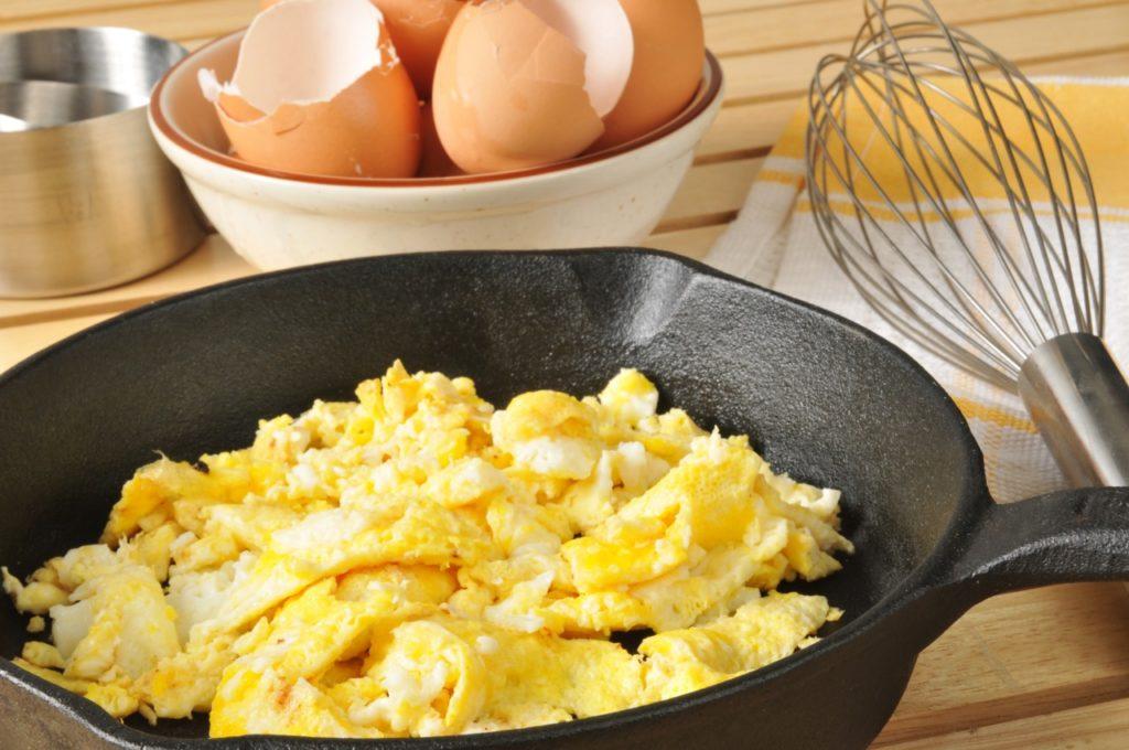 Frigideira de ferro com ovos mexidos. No fundo da imagem, cascas de ovos quebrados e um batedor de claras ao lado.