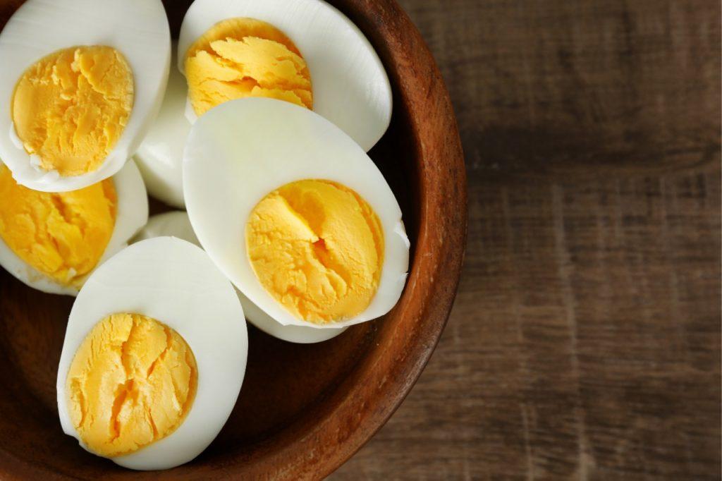 Três ovos cozidos cortados ao meio, dentro de uma tigela rústica.