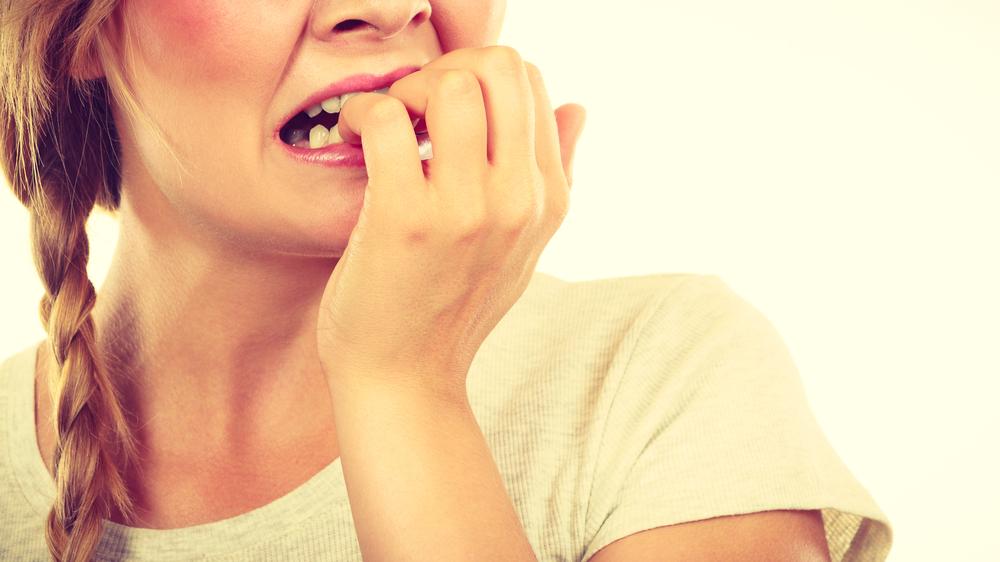 Mulher com trança, camiseta bege, com a mão esquerda sobre os dentes mostrando ansiedade.
