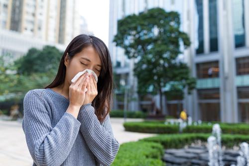 mulher asiática com lenço de papel no rosto enquanto espirra
