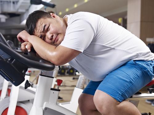 homem oriental cansado em cima de uma bicicleta ergométrica