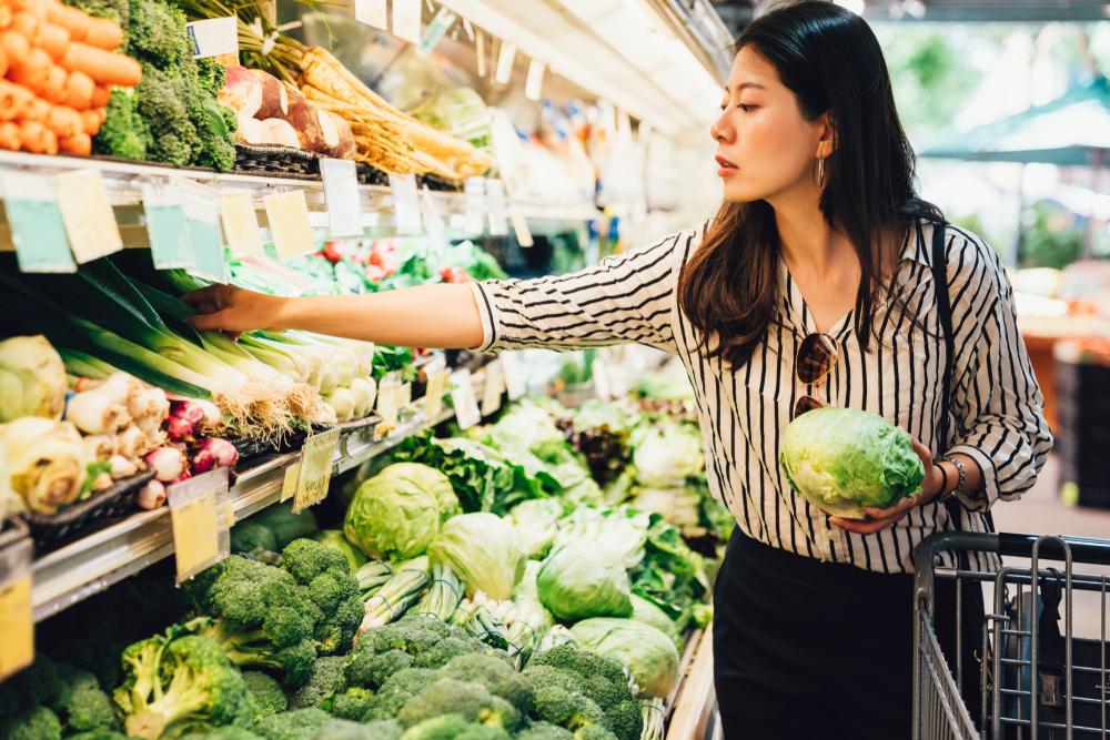Alimentação saudável na quarentena: mulher asiática fazendo compras na seção de hortaliças do supermercado.