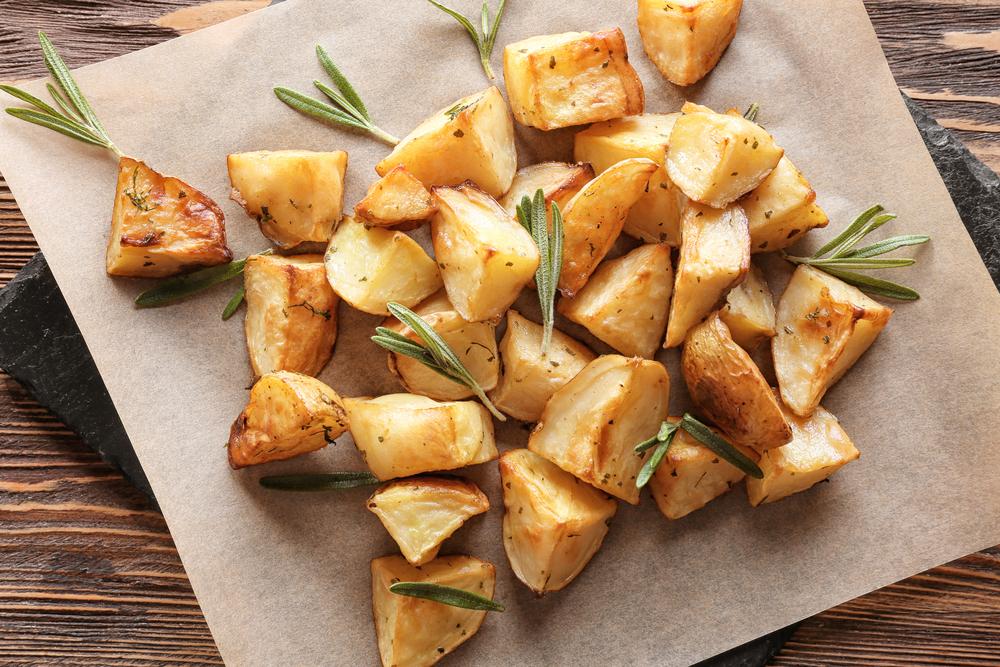 Alimentação saudável na quarentena: prato com batatas cortadas em cubos com folhas de alecrim.