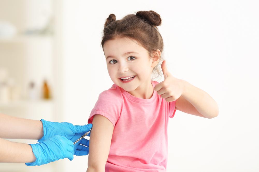 criança sorrindo fazendo sinal de positivo enquanto recebe vacina