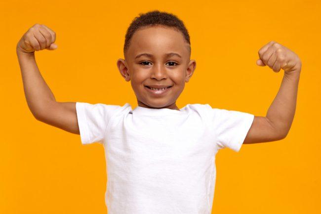 criança negra sorrindo tensionando os músculos do braço