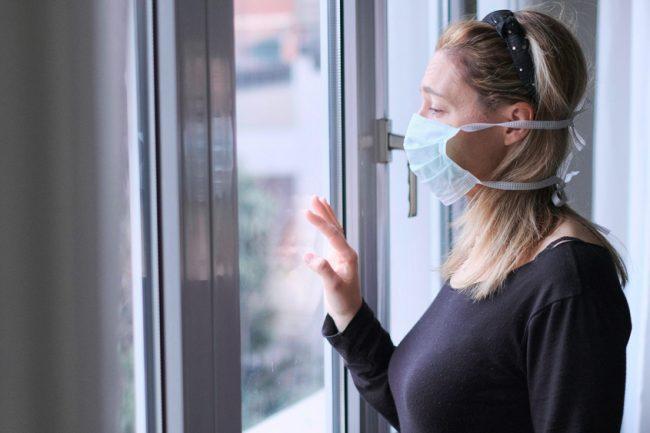 mulher com máscara em frente a janela