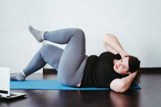 Mulher fazendo aula online de abdominal