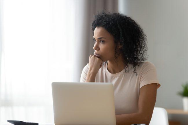 mulher afrodescendente usando o computador com expressão de reflexão