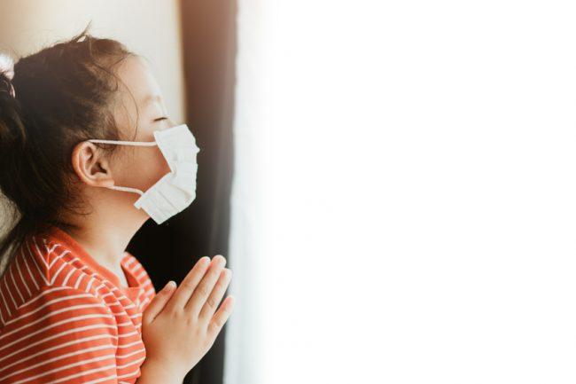 Criança de máscara olhando pela janela com mãos postas em oração
