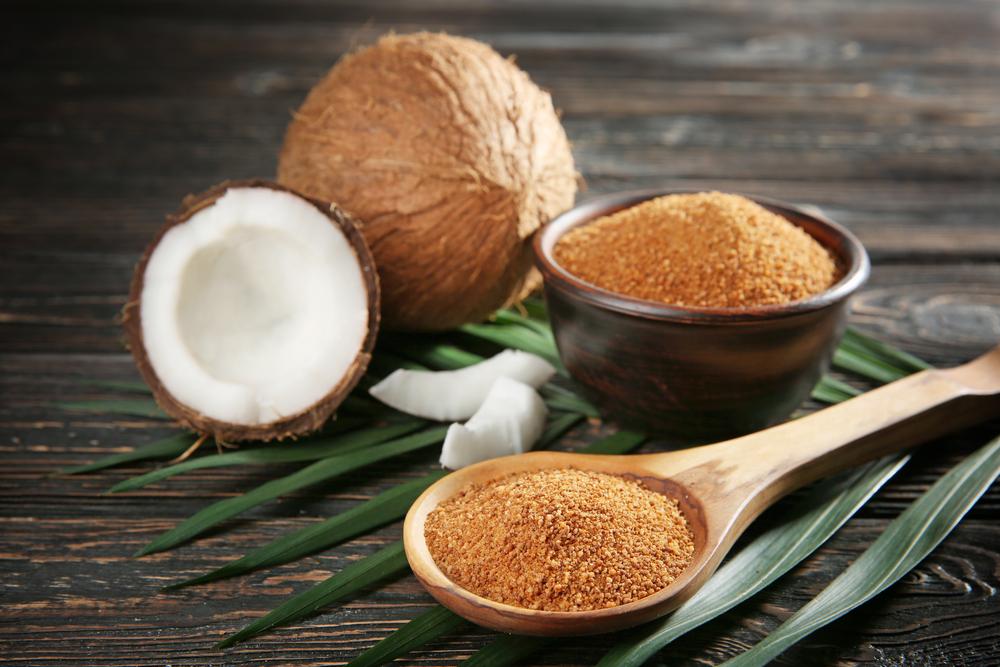 Colher com açúcar de coco e metade de um coco aberto