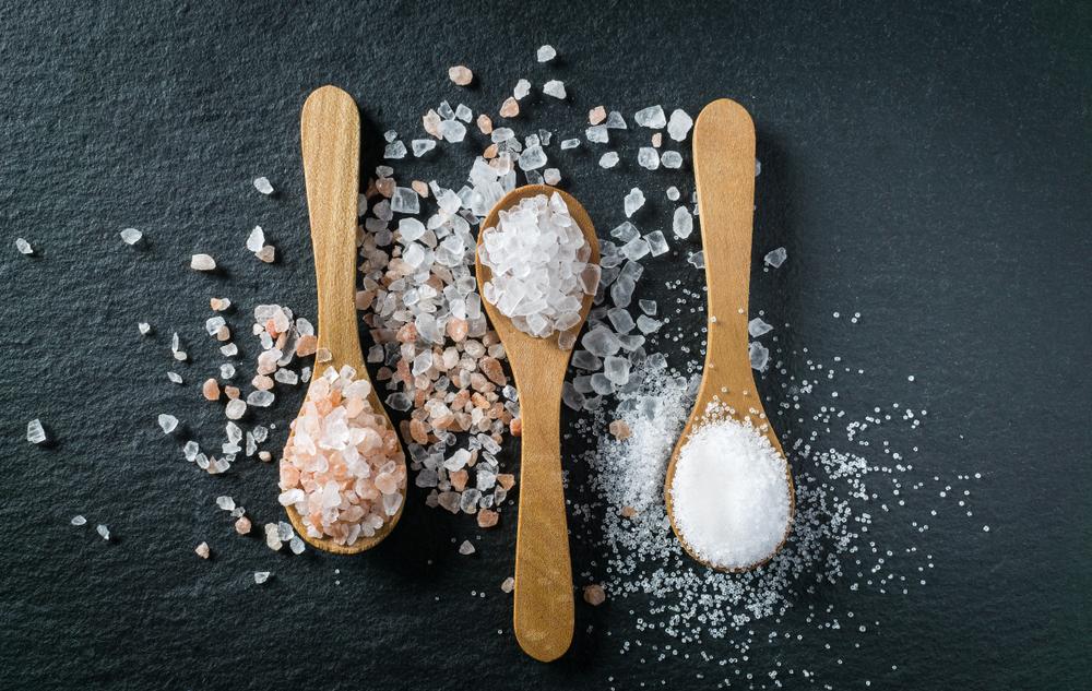 três colheres contendo um tipo de sal cada uma